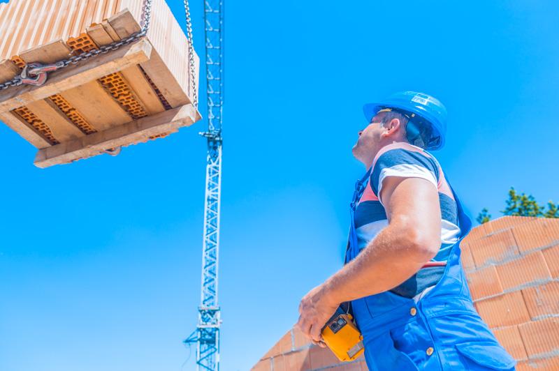 Crane driver deliver a pallet bricks on construction or building site